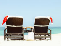 Christmas card or background - couple in sunloungers with Santa. Hats standing on beautiful tropical beach with white sand and turquoise water. Concept of Stock Photo