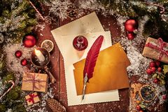 Christmas card background with letter, envelopes and vintage red feather quill pen surrounded by gifts, pine and baubles lit by a. Burning candle stock image