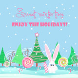 Christmas card background. Rabbit with sweets candy in the christmas tree forest. Royalty Free Stock Photos
