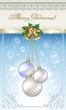 Christmas card with balls on a blue background. Decorated with golden ribbon and bells Royalty Free Stock Images