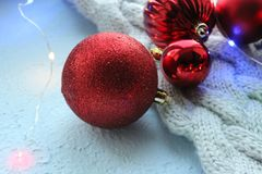 Christmas card. Beautiful Christmas background. Lots of red balls big and small on blue texture background. White snowflakes circl. Ing, the effect of falling stock photography