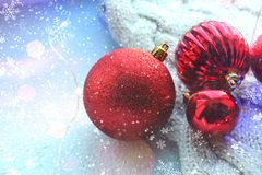 Christmas card. Beautiful Christmas background. Lots of red balls big and small on blue texture background. White snowflakes circl. Ing, the effect of falling royalty free stock photography