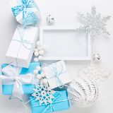 Christmas card with beautiful blue and white decorations. Christmas greeting card with empty white frame, blue and white holiday decoration, ball and toys on a royalty free stock images