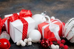 Christmas card with beautiful red and white decorations. Red and white gifts boxes with ribbon and holiday decoration, ball and toys on a dark background stock images