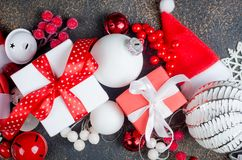 Christmas card with beautiful red and white decorations. Red and white gifts boxes with ribbon and holiday decoration, ball and toys on a dark background royalty free stock photos