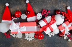 Christmas card with beautiful red and white decorations. Red and white gifts boxes with ribbon and holiday decoration, ball and toys on a dark background royalty free stock photo