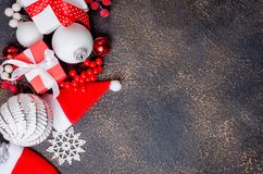 Christmas card with beautiful red and white decorations. Red and white gifts boxes with ribbon and holiday decoration, ball and toys on a dark background royalty free stock photography