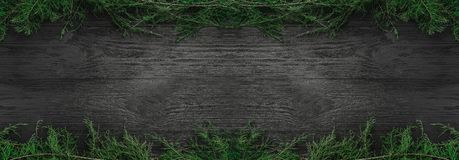 Christmas card. Black wood background with fir branches up and down, top view. Xmas rectangle congratulation stock photos