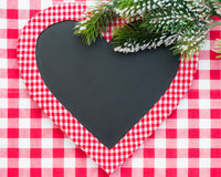 Christmas card blank in heart shape. Card blank in heart shape with branch of Christmas tree on red gingham tablecloth. Winter holidays concept Stock Image