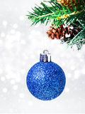 Christmas card with blue hanging ball and pine branch on Defocus Royalty Free Stock Photo
