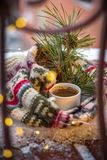 Christmas card. A branch of spruce with pine cones, a scarf and a cup of coffee in the snow stock images