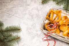 Christmas card. The branch of the tree is spruce. Cookies in a wicker basket on a white background. Christmas card. The branch of the tree is spruce. Cookies in Stock Image