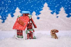 Christmas card with a Bunny and a house near the forest in the snow. Christmas card with a cute Bunny and a winter house with a red roof near the forest in the Stock Photo