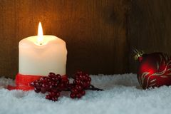 Christmas card with burning candle. Burning candle with red ribbon, red berries and Christmas ball in snow Stock Images