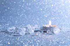 Christmas card with a burning candle on a silver background. Candle and glass beads on a silver background. Festive composition Royalty Free Stock Image
