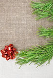 Christmas card with canvas, fir branch and bow on burlap Royalty Free Stock Image