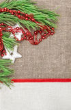 Christmas card with canvas, fir branch and garland on burlap Royalty Free Stock Photos
