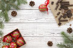 Christmas Card with chocolate candies, christmas decorations and fir branches on white wooden background Royalty Free Stock Photo