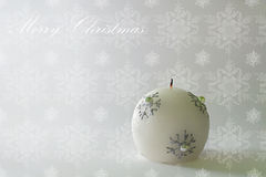 Photo of a christmas candle on a simple and elegant snowflakes decorated background - Christmas card Stock Photo