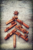 Christmas card with Christmas fir tree made from spices cinnamon sticks, anise star and cane sugar on rustic wooden background Stock Photos