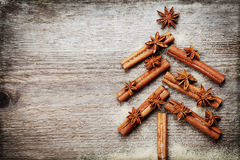 Christmas card with Christmas fir tree made from spices cinnamon sticks, anise star and cane sugar on rustic wooden background. Vintage toned, copy space for Royalty Free Stock Image