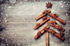 Christmas card with Christmas fir tree made from spices cinnamon sticks, anise star and cane sugar on rustic wooden background. Magic snow effect, vintage royalty free stock photos