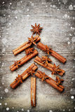 Christmas card with Christmas fir tree made from spices cinnamon sticks, anise star and cane sugar on rustic wooden background, ma Stock Images