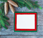 Christmas card with christmas natural decorations. Greeting card for the Christmas holidays . Spruce branches. Empty paper sheet on rustic table from above Royalty Free Stock Photos