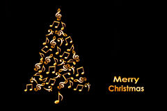 Christmas card with a Christmas tree made of shiny golden musical notes on black. Background Stock Images