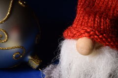 Christmas card - closeup of gnome and ball on blue backdrop Stock Images