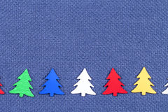 Christmas card with colorful  Christmas trees on a background of blue fabric Stock Photography