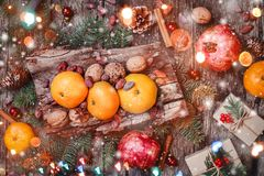 Christmas card. Christmas gifts, pomegranate, Tangerines, Nuts, cocoa beans, Fir branches on wooden snowy background. Xmas and Happy New Year composition. Top stock photography