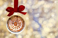 Cup of fragrant hot coffee with white foam and cinnamon snowflake made from Christmas ball, bauble hangs on a red ribbon stock photos