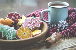A cup of hot tea stands on a wooden table next to a wooden plate on which are gingerbread cookies made from orange stock photography