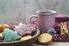 A cup of hot tea stands on a wooden table next to a wooden plate on which are gingerbread cookies made from orange royalty free stock photos