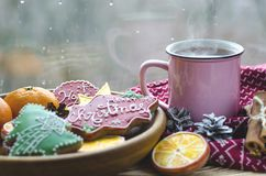 A cup of hot tea stands on a wooden table next to a wooden plate on which are gingerbread cookies made from orange royalty free stock image