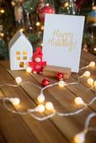 Christmas card with lights and decorations. Christmas card with decorated tree on background, lights and house and ornaments in red gold color, place for text Royalty Free Stock Images
