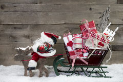 Christmas card decoration: elks pulling santa sleigh of presents. Christmas card decoration: elks pulling santa sleigh with presents on a wooden background Stock Photography