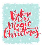 Christmas card design. Believe in the magic of Christmas. Inspirational xmas quote. Red brush calligraphy text on blue Stock Image