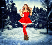 Christmas card design sexy woman. Christmas card design - beautiful sexy woman wearing santa claus clothes stay in the snow forest Stock Image