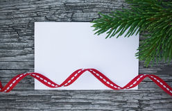 Christmas card: empty paper form with fir-tree branches on wooden background Stock Photos