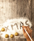 Christmas card with a female hand writing xmas, gold balls in the snow on a wooden background. Royalty Free Stock Photo