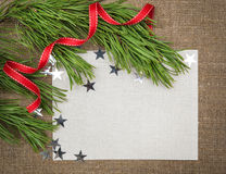 Christmas card with fir branch, stars and red ribbon on burlap Stock Photography