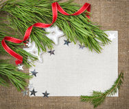 Christmas card with fir branch, stars and red ribbon on burlap Royalty Free Stock Photography
