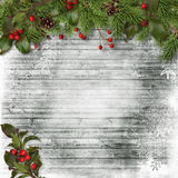 Christmas card. Fir branches and holly on a wooden background Stock Photos