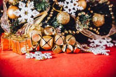 Christmas card with fir tree branch decorated with golden baubles, garlands and vintage snowflakes on a red background. Royalty Free Stock Photo