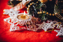 Christmas card with fir tree branch decorated with golden baubles, garlands and vintage snowflakes on a red background. Stock Images