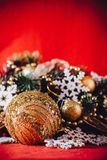 Christmas card with fir tree branch decorated with golden baubles, garlands and vintage snowflakes on a red background. Royalty Free Stock Photos
