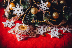 Christmas card with fir tree branch decorated with golden baubles, garlands and vintage snowflakes on a red background. Stock Image