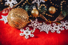 Christmas card with fir tree branch decorated with golden baubles, garlands and vintage snowflakes on a red background. Royalty Free Stock Images